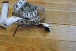 fabric tape measure lying on a wood fllor