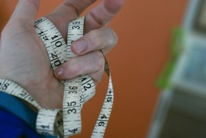Fabric tape measure held in a hand.